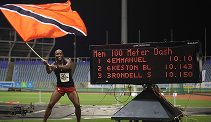 NEW SPRINT KING Emmanuel Callender of Memphis Pioneers waves the national flag in celebration of his triumph in the men's 100 metres sprint finals during the NAAA NGC/Sagicor National Championships at the Hasely Crawford Stadium on Saturday night. Callender clocked 10.10 seconds. Photo: Allan V. Crane/CA-images