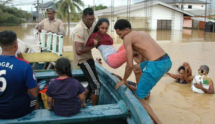 Ravi Kalpoo, centre, of Klapoo Tours is assisted by a villager during efforts to help marooned flood victims in central Trinidad.  -Photo: Courtesy Kalpoo Tours