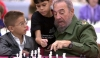 Former President of Cuba Fidel Castro playing a game of Chess with two young Cuban boys.