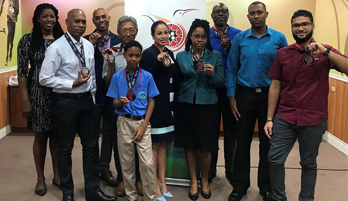 Runners, who completed the BAFA Sports/TTOC Virtual 5K, pose with their medals during a distribution ceremony at TTOC Olympic House, Abercromby St, Port of Spain, yesterday.