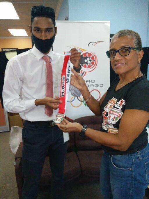 TOP TIME: Corey Joseph-Samaroo, left, receives his virtual Trinidad and Tobago International Marathon (TTIM) medal from TTIM chairperson Diane Henderson, at the T&T Olympic Committee (TTOC) office, Abercromby Street, Port of Spain, on Thursday. Joseph-Samaroo recorded the fastest time in the event, the One-A-Week runner completing 26.2 miles in three hours, 17 minutes and 38 seconds.