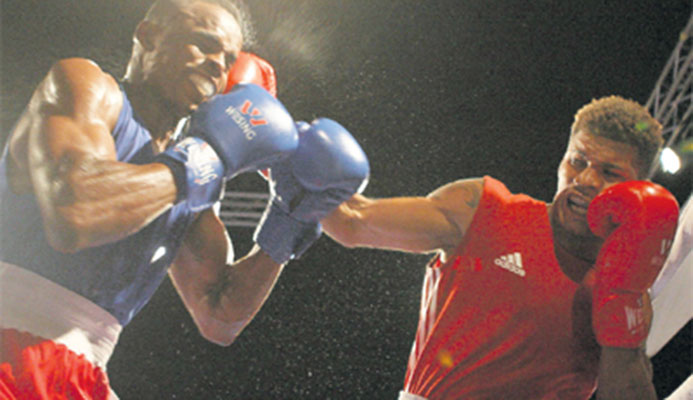 T&T's Michael Alexander, right, catches Jamaica's Damion Williams with a punch to the head, during Tuesday night's Boxing At the Castle duel. Alexander won the fight by unanimous decision. PHOTO: WALTER ALIBEY